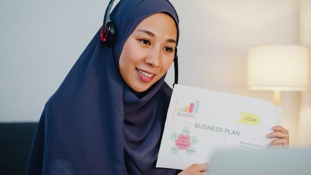 La dama musulmana usa auriculares usando una computadora portátil, hable con sus colegas sobre el informe de venta en una videoconferencia mientras trabaja desde la oficina en casa por la noche.
