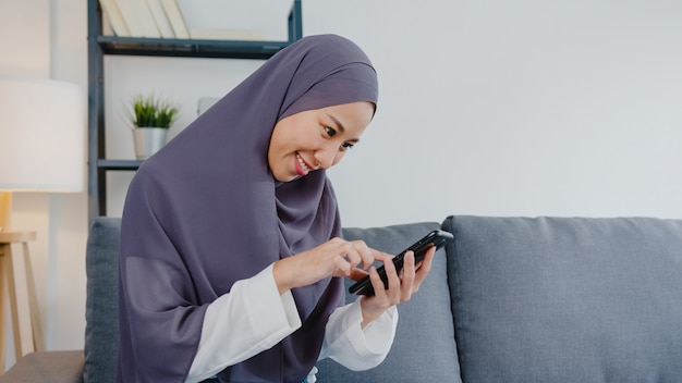 La dama musulmana usa un teléfono inteligente y compra internet de comercio electrónico en el sofá de la sala de estar de la casa.