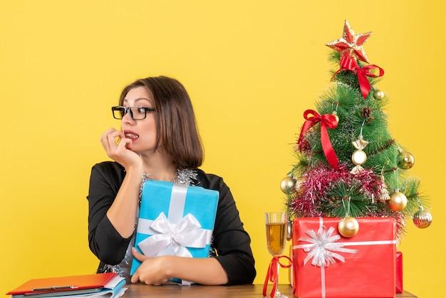 Dama de negocios confundida sorprendida emocional en traje con gafas sosteniendo su regalo y sentada en una mesa con un árbol de navidad en la oficina