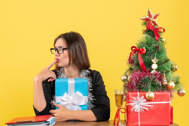 Dama de negocios confundida sorprendida en traje con gafas sosteniendo su regalo y sentada en una mesa con un árbol de navidad en la oficina