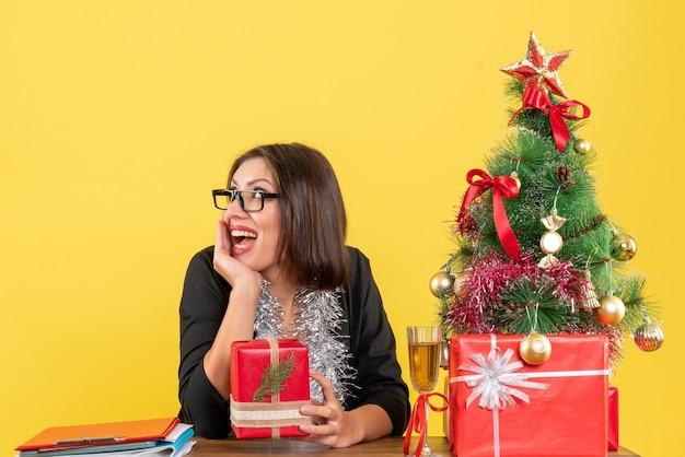 Dama de negocios sorprendida en traje con gafas mostrando su regalo y sentada en una mesa con un árbol de navidad en la oficina