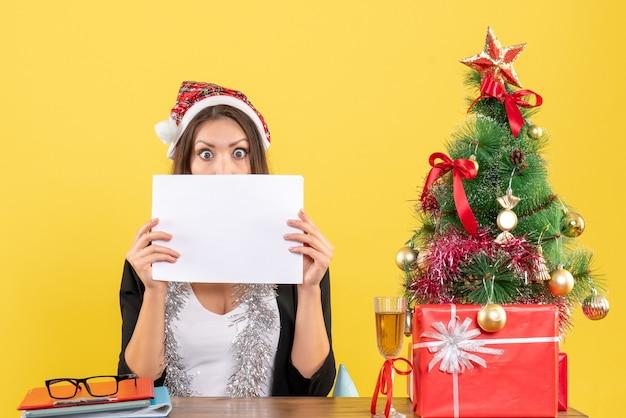Dama de negocios sorprendida en traje con sombrero de santa claus y decoraciones de año nuevo trabajando solo y sentado en una mesa con un árbol de navidad en la oficina