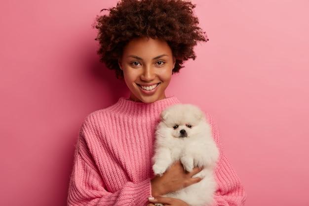 Dama de piel oscura mantiene los labios redondeados, quiere besar a una adorable mascota, juega con un pequeño cachorro