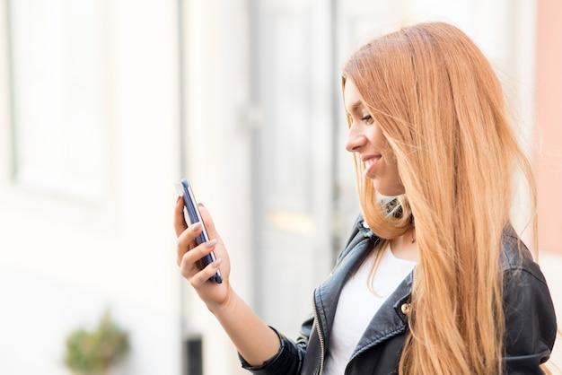Dama positiva haciendo video llamada en el teléfono inteligente