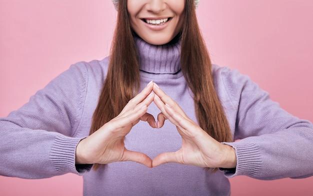 La dama que usa un suéter delicadamente púrpura muestra un corazón de dedos