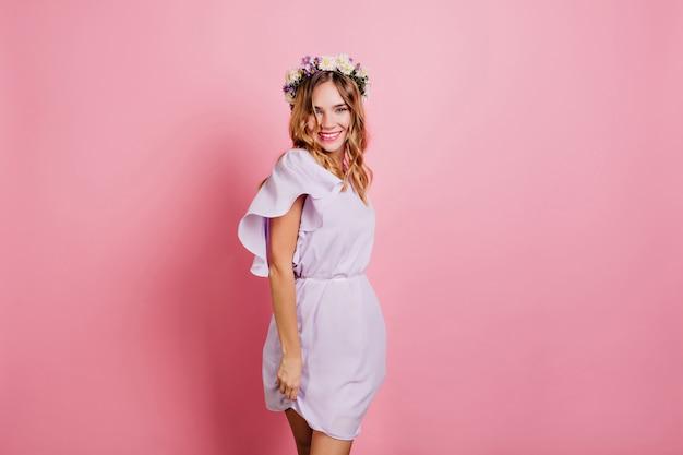 Dama riendo bien formada con peinado ondulado romántico bailando en la pared rosa