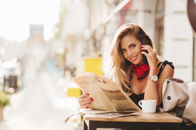 Dama romántica con periódico posando en la cafetería con bonita sonrisa, con multitud en el fondo