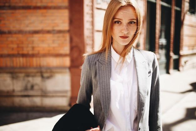 Dama rubia en traje gris disfruta del sol en la calle brillante de la ciudad de nueva york
