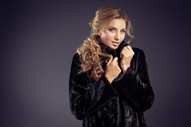Dama seductora de cabello rubio con un elegante abrigo de piel y ropa interior negra
