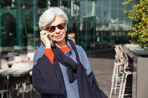 Dama senior alegre que aprende buenas noticias de la conversación telefónica