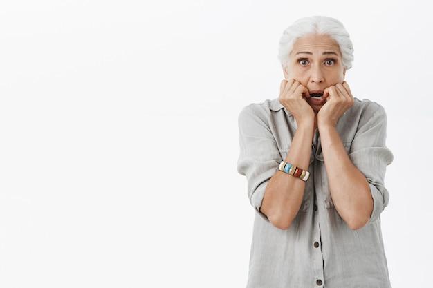 Dama senior insegura asustada jadeando emboscada y mirando asustada