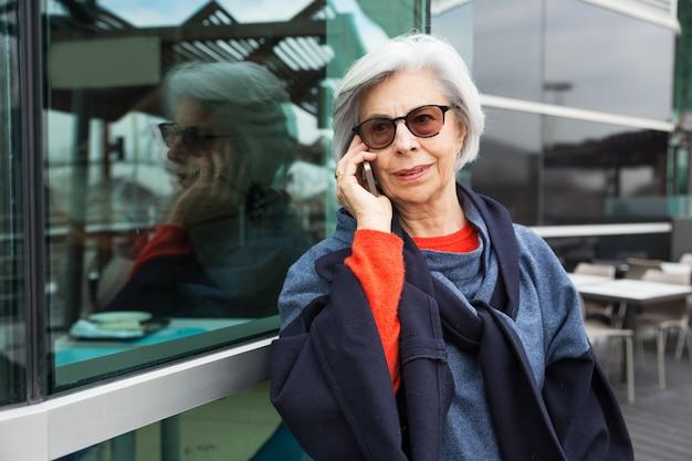 Dama senior positiva en gafas de sol hablando por celular