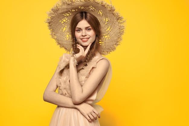 Dama con sombrero y vestido rojo pelo fondo amarillo modelo retrato divertido. foto de alta calidad