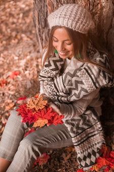 Dama sonriente con hojas sentado cerca de un árbol