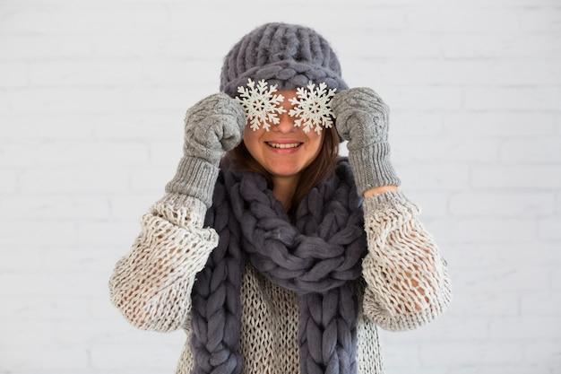 Dama sonriente en mitones, bufanda y sombrero con adornos copos de nieve en los ojos
