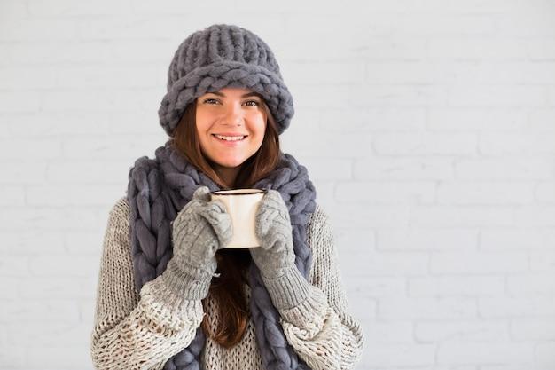 Dama sonriente en mitones, gorro y bufanda con taza en las manos