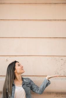 Dama sonriente con la palma hacia arriba gesto