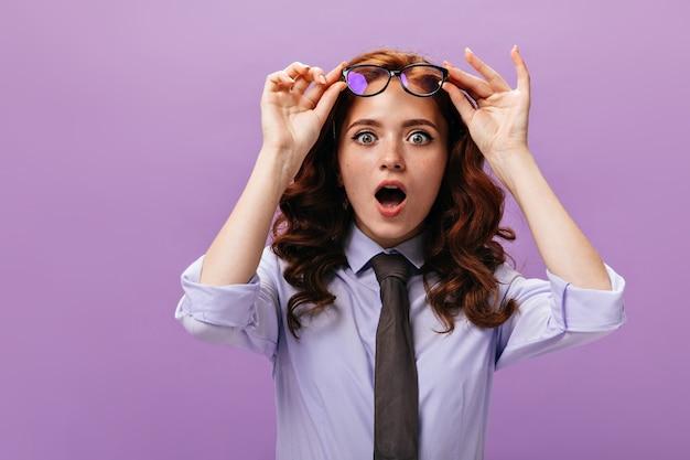 Dama sorprendida se quita los anteojos en la pared púrpura