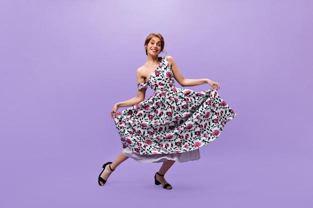 Dama con vestido estampado floral hace reverencia. sonriente mujer de moda en ropa de verano brillante moderno posando sobre fondo aislado.