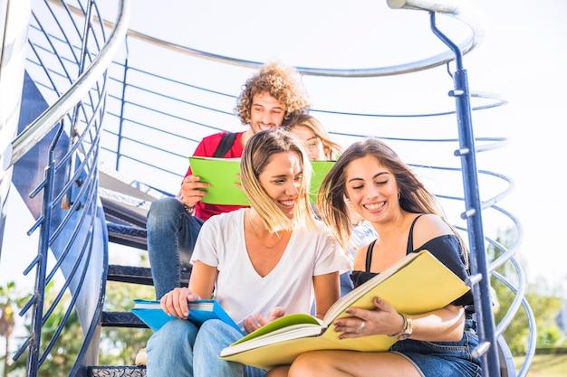 Damas estudiando en la escalera cerca de amigos