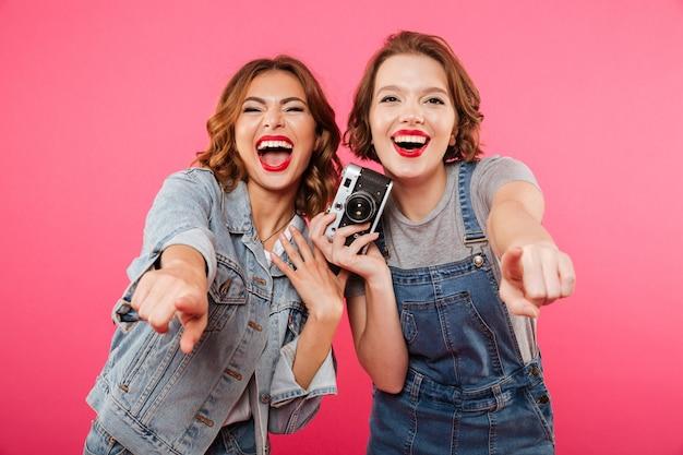 Las damas felices hacen una foto con la cámara y te señalan.