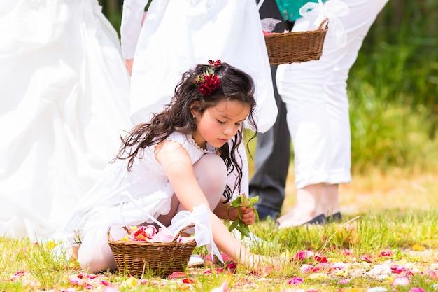 Damas de honor de boda con cesta de pétalos de flores.