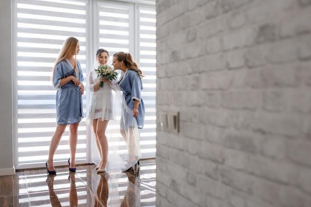 Las damas de honor con la novia vestida con ropa de dormir sedosa están oliendo el aroma de un ramo de boda