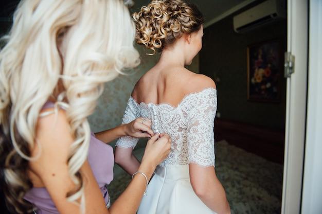 Damas de honor que ayudan a llevar un vestido de novia de encaje