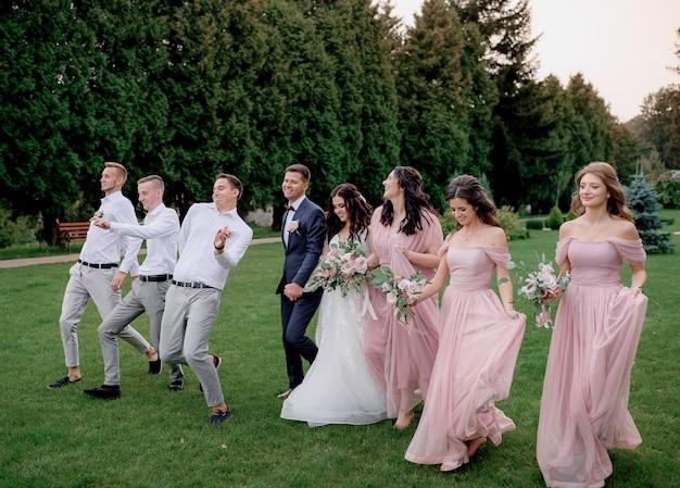 Las damas de honor vestidas con vestidos de color rosa, los mejores hombres y la pareja de novios están felizmente caminando en el patio verde