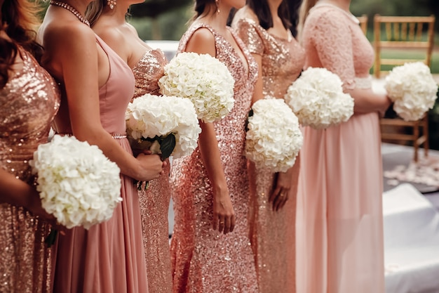 Las damas de honor en vestidos rosados se colocan con los ramos de flores blancas en