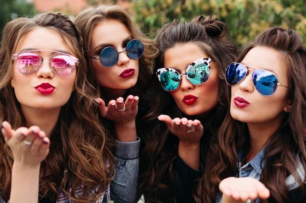 Damas de moda con peinado tomando selfie al aire libre.