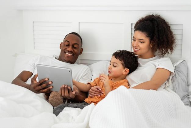 Dan leyendo algo en una tableta mientras está en la cama con su familia