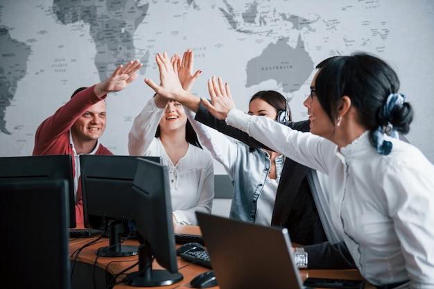 Dando cinco. jóvenes que trabajan en el centro de llamadas. se acercan nuevas ofertas