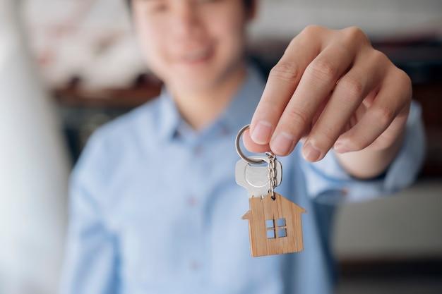 Dando, ofreciendo, demostrando, sosteniendo las llaves de la casa.