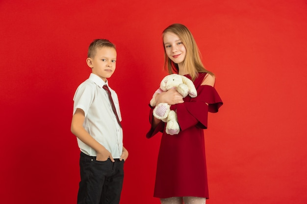 Dando suavidad. celebración del día de san valentín, felices, lindos niños caucásicos aislados sobre fondo rojo de estudio. concepto de emociones humanas, expresión facial, amor, relaciones, vacaciones románticas.