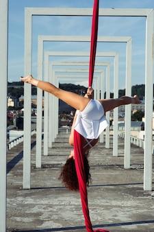 Danza aérea en la azotea, bailarina de seda morena sexy en vestido blanco