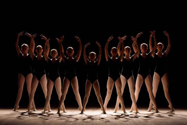 Una danza coreografiada de un grupo de agraciadas bailarinas jóvenes practicando en el escenario de una escuela de ballet clásico.
