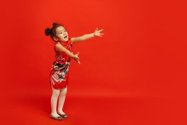 Dar un abrazo a amigos y familiares. . niña linda asiática aislada en la pared roja en ropa tradicional. celebración, emociones humanas, concepto de vacaciones. copyspace.