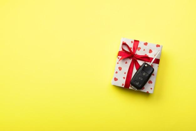 Dar el concepto clave de coche de regalo vista superior. caja actual con lazo de cinta roja, corazón y llave del auto sobre fondo de color amarillo