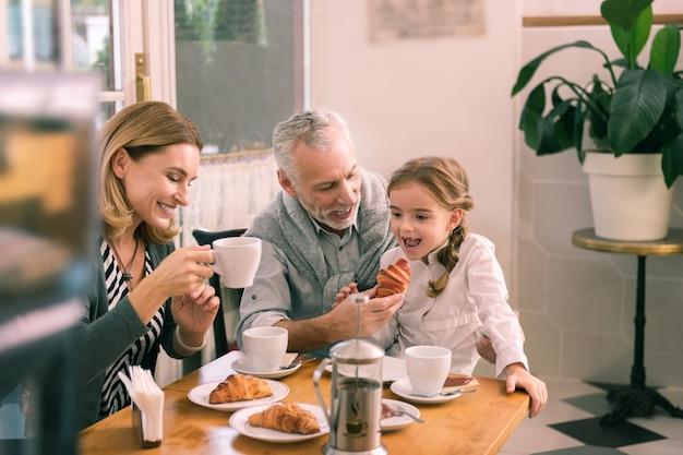 Dar croissant. abuelo canoso sonriente dando croissant a su niña desayunando en familia