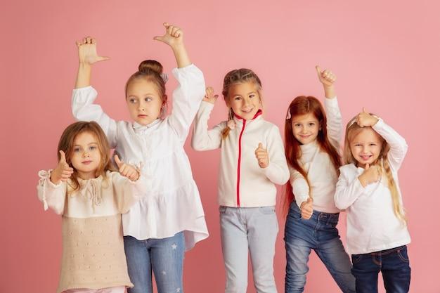 Dar y recibir regalos en navidad. grupo de niños sonrientes felices divirtiéndose, celebrando aislado sobre fondo rosa studio. reunión de año nuevo 2021, infancia, felicidad, emociones.