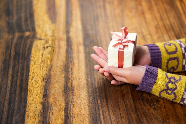 Dar un regalo en el fondo de madera, vista desde arriba