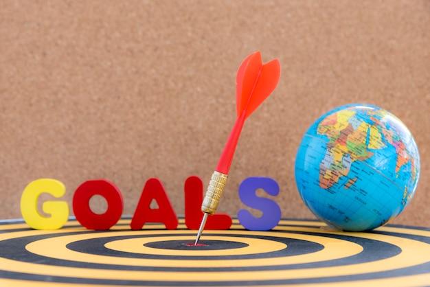 Dardo objetivo en diana con los objetivos de la palabra y el globo