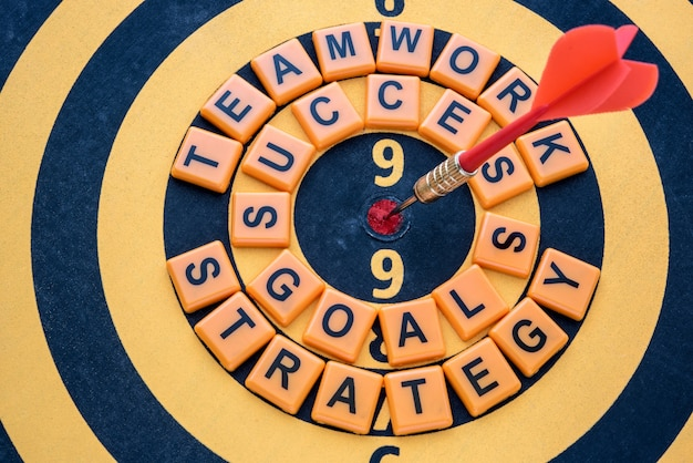 Dardo objetivo en diana con palabras de éxito