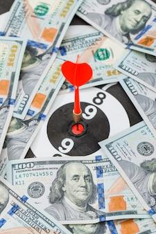 Dardo rojo en el centro del tablero de dardos en billetes