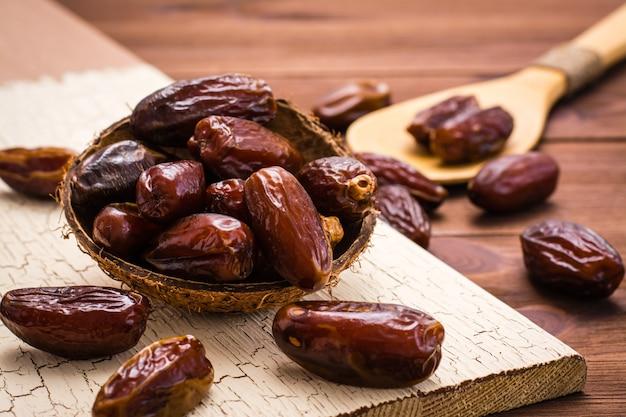 Dátiles dulces secos fruta en un tazón de madera y en la cuchara sobre la mesa