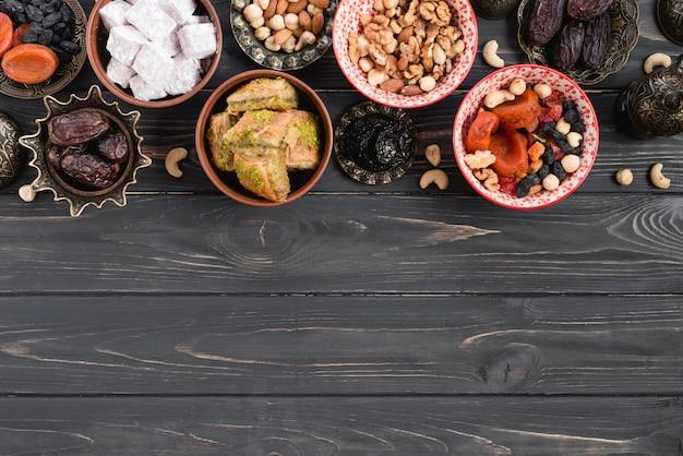 Dátiles orgánicos crudos secos; frutas secas; nueces; lukum y baklava en mesa de madera negra