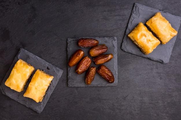 Dátiles secos frutales con dulces orientales sobre mesa negra.
