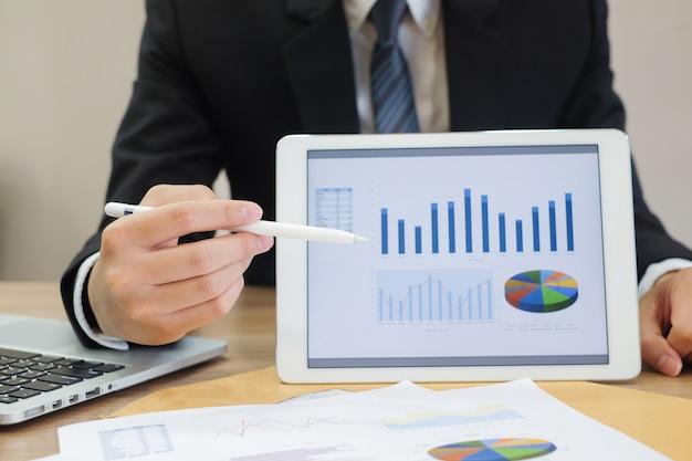 Datos de tablero de muestra de empresario en tableta y mano apuntando para explicar estadística