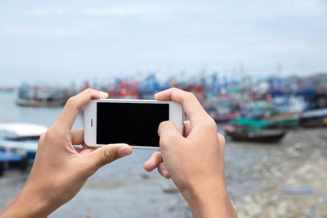 Dé a control el teléfono móvil blanco con el mar y el puerto frescos hermosos.
